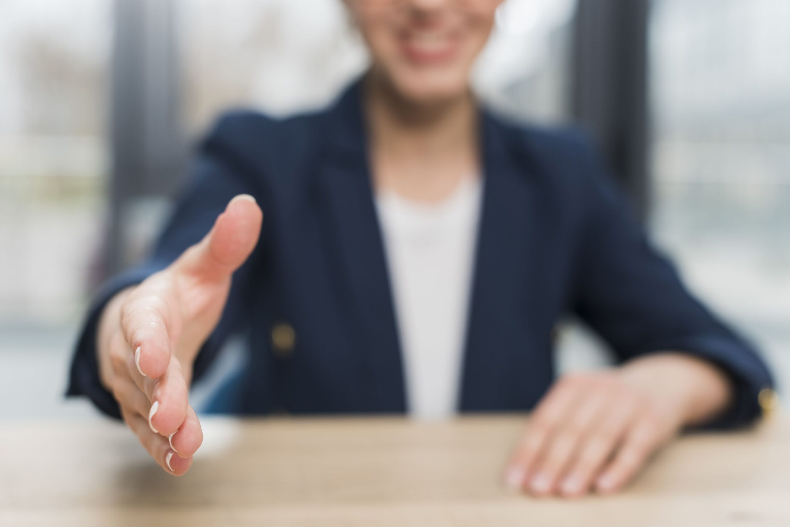 front view defocused woman offering hand shake after being hired scaled